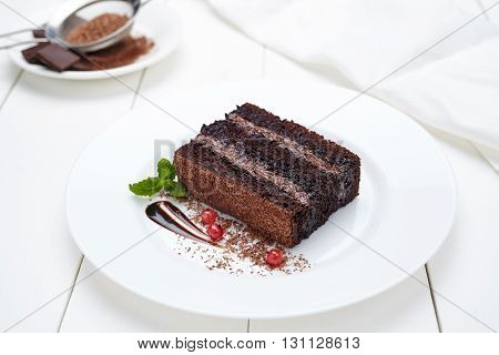 Chocolate brownie cake with cocoa cream and berry sauce in white plate. Delicious pastry dessert.