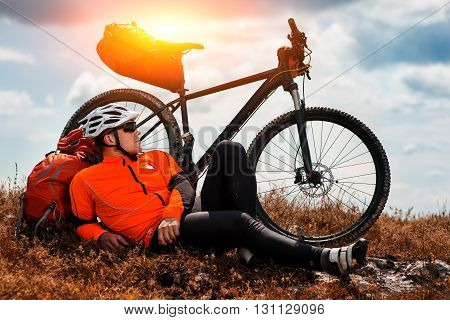 Young man cycling on a rural road through green spring meadow during sunset
