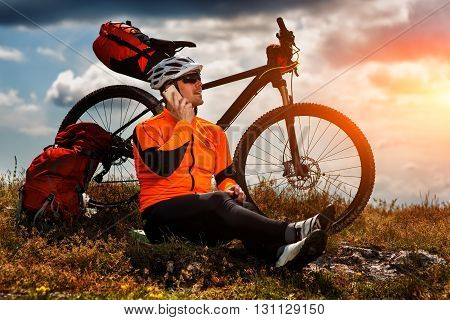 Sportive Young Man In Red Shirt Stops Cycling and Has a Rest on a Valley and Talking on the Phone