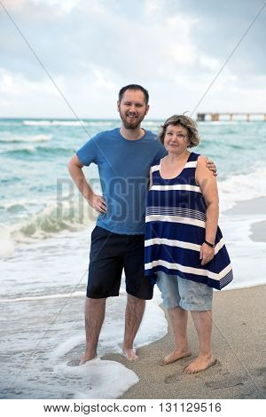 Adult mother with her son at the beach. Family content