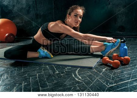 Beautiful young slim woman doing stretching exercises at the gym with orange dumbbells