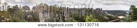 Panorama Bastei. Saxon Switzerland in the autumn. Gloomy skies drizzling rain.Turisty walking on the bridge.