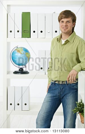 Young environmentalist man standing in office looking at camera, smiling.?