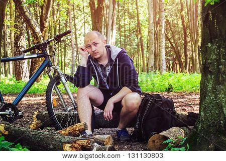 Cyclist with backpack young man thinking with fatigue on face in beautiful forest summertime journey