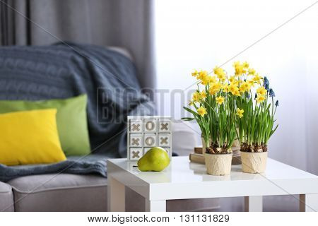 Blooming narcissus flowers and pear fruit on table indoors