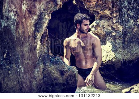 Attractive young athletic man in the sea or ocean by the rocky shore, showing naked muscular torso, serious expression