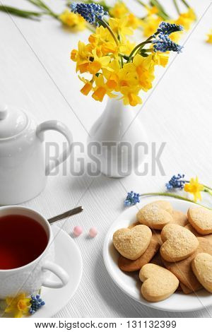 Narcissus flowers with cup of tea and cookies on wooden background