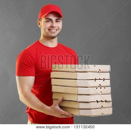 Young handsome man with pizza on grey background