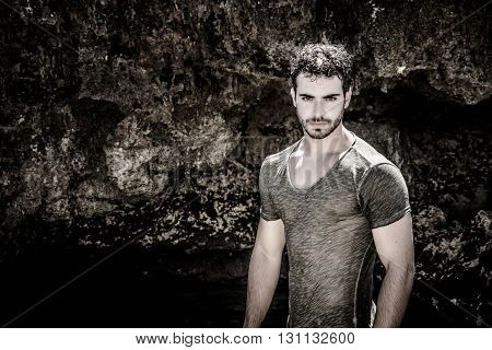 Attractive young athletic man in the sea or ocean by the rocky shore, wearing wet t-shirt, serious expression