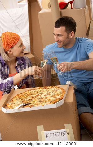 Happy couple having pizza and clinking champagne glasses at lunch break of moving house.?