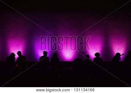 Silhouettes of people sitting in front of a wall lighted with colored spots