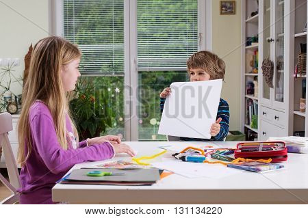 Boy sitting at table holding blank piece of paper showing it to his sister or friend. Copy space for text or drawing painting. Children expressing creativity learning by doing learning through experience.
