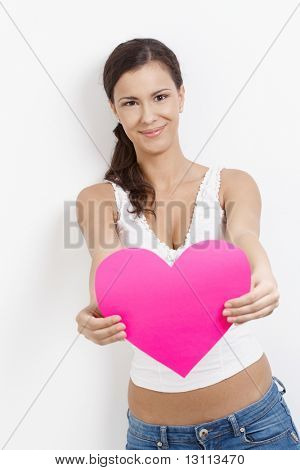 Lovesick young attractive woman smiling happily with pink paper heart in hands.?