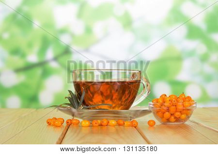 A bowl of sea buckthorn berries and a cup of tea on the abstract green background.