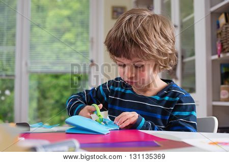 Cute little boy cutting shapes out of colored paper. Being creative developing imagination creativity do it yourself concept.