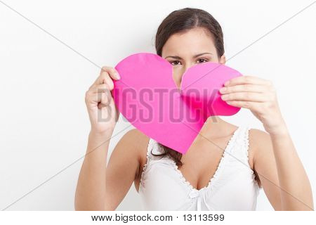 Young woman pulling pink paper heart to pieces.?