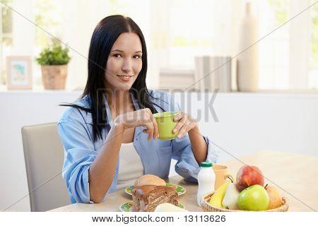 Sorrindo bela mulher sentado à mesa do pequeno-almoço, segurando o copo, olhando para a câmera.