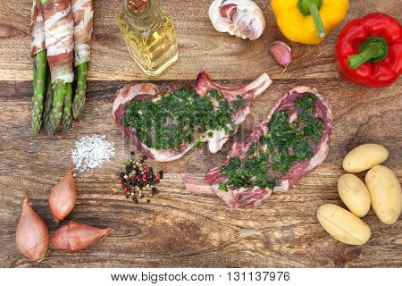 Fresh cutlets in a herb marinade with ingredients for grilling