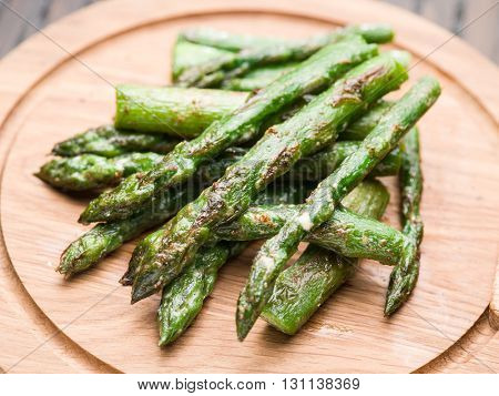 Cooked asparagus sprouts on the wooden tray.