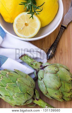 Organic fresh artichokes with lemon on a white table. Selective focus, top view