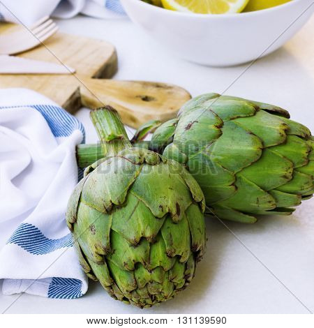 Organic fresh artichokes with lemon on a white table. Ingredients for healthy eating. Selective focus