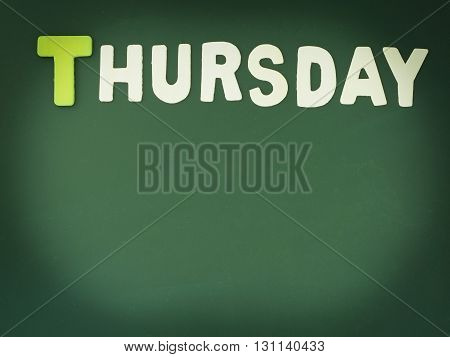 Wooden Thursday on Green Board. Wood Thursday word on blackboard with copy space.