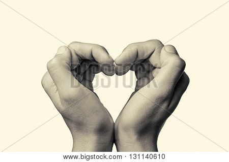 girl's hands serried in a heart shape on isolated toned background