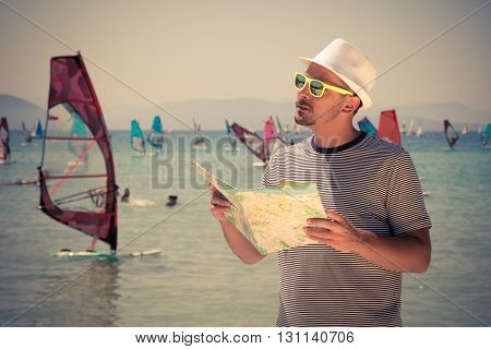 Guy trying to find the right direction by using his map. Windsurfers in the background.