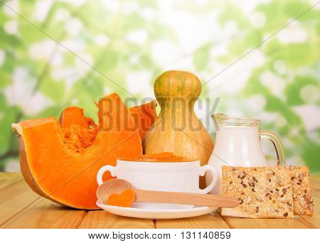 Serve soup with pumpkin, a jug of milk and cookies on abstract green background.