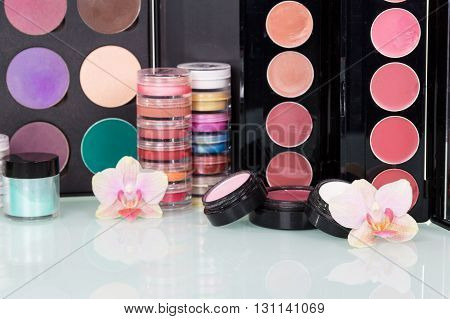 Set of professional cosmetic makeup and orchid flowers background.