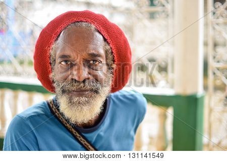Bluefields Nicaragua - July 15 2015: Elderly rasta man wears a red rasta hat which hides his long grey dreadlocks on July 15 2015 in Bluefields Nicaragua