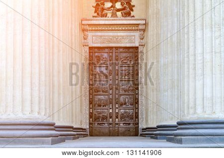 The bronze doors and the colonnade of the Kazan Cathedral in Saint-Petersburg Russia under soft sunlight