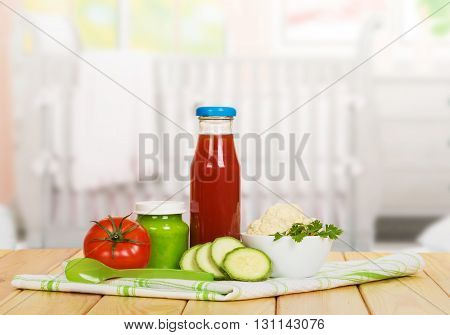 A bottle of tomato juice, vegetable puree bank, bowl with cauliflower, squash, cotton napkin and spoon on a background of the kitchen.