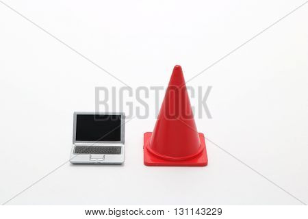 Miniature laptop and safety cone on white background.