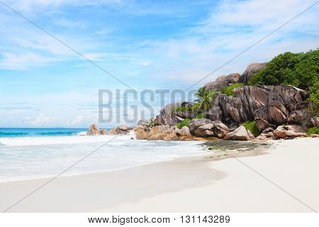 Scenic tropical  beach  with white sand, turquoise ocean water,  granite rocks and  blue sky