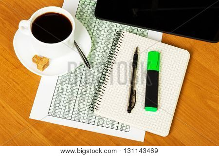 Digital tablet, notebook, pen, marker, and a cup of coffee on the background of the desktop.