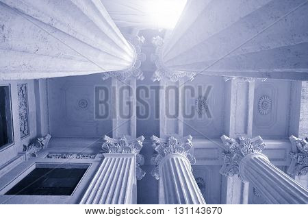 Closeup of colonnade tops and the ornanental ceiling of famous Kazan Cathedral under soft sunlight in Saint-Petersburg Russia. Black and white cold tones applied