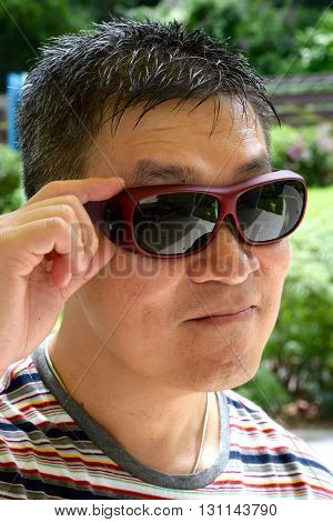 An asian man wearing in sunglasses in a cheeky manner