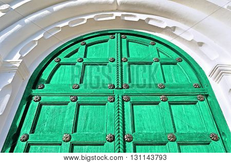 Architecture detailed background - aged wooden door of bright green color with metal rivets and upper arch of white stone - vintage architecture background
