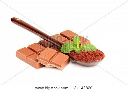 Bar of milk chocolate with a spoonful of cocoa powder and a sprig of mint.