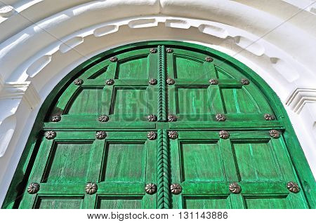Architecture detailed background - aged wooden door of magenta color with metal rivets and upper arch of white stone - vintage architecture background