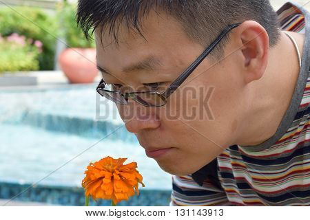An asian man smelling an orange flower outdoor