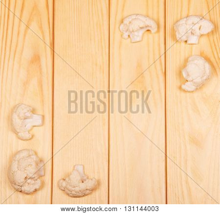 Pieces of raw cauliflower close-up on a background of light wood.
