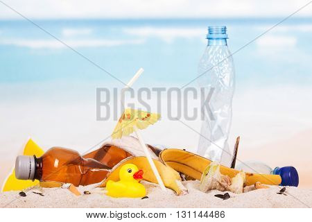 Plastic bottles, food waste and a rubber duck in the sand against the sea.