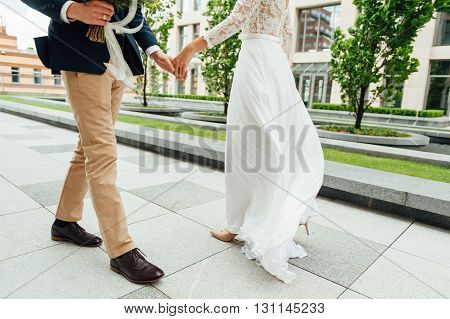 Lovers Is Running With Hold Hands On City Park