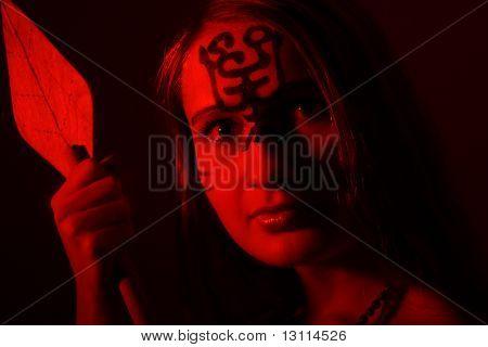 Shot of an girl holding african spear. Shot in studio.