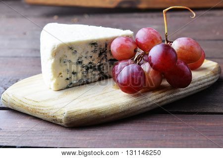pieces of blue cheese and red grapes on a wooden table