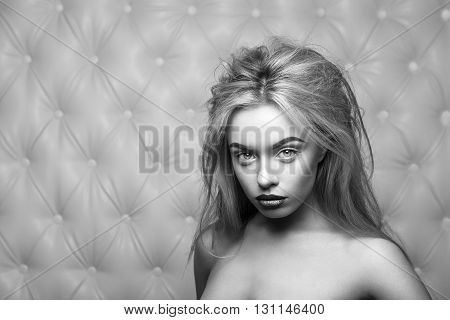 Studio portrait of a sexy blond, over leather upholstery background. Elegant luxury woman with a seductive neckline and bare shoulders looks into the camera. Black and white photo.
