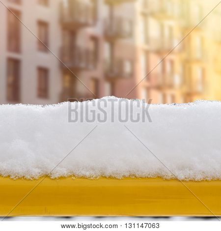 snow on the yellow bench in the yard, apartments background