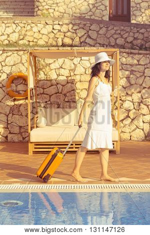 Young woman carrying orange luggage and arriving to the resort. She is walking next to the swimming pool. Beginning of summer vacation concept.